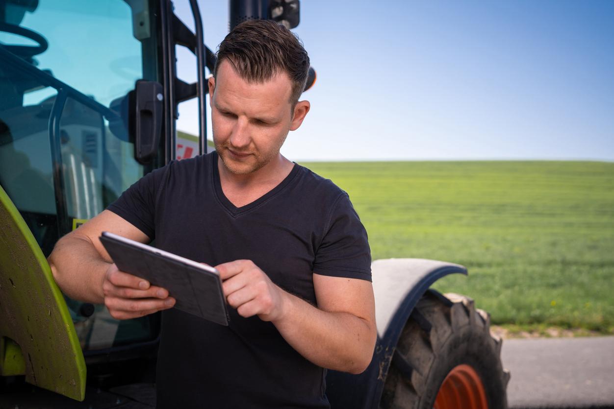 Mann mit Tablet, der sich auf dem Acker ein Online-Seminar von JOSERA und FarmCHAMPs ansieht